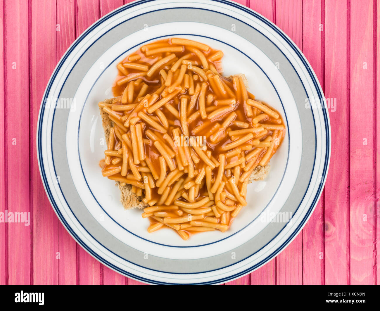 Spaghetti on Toasted Bread Served on a Plate Against a Pink Background - Stock Image