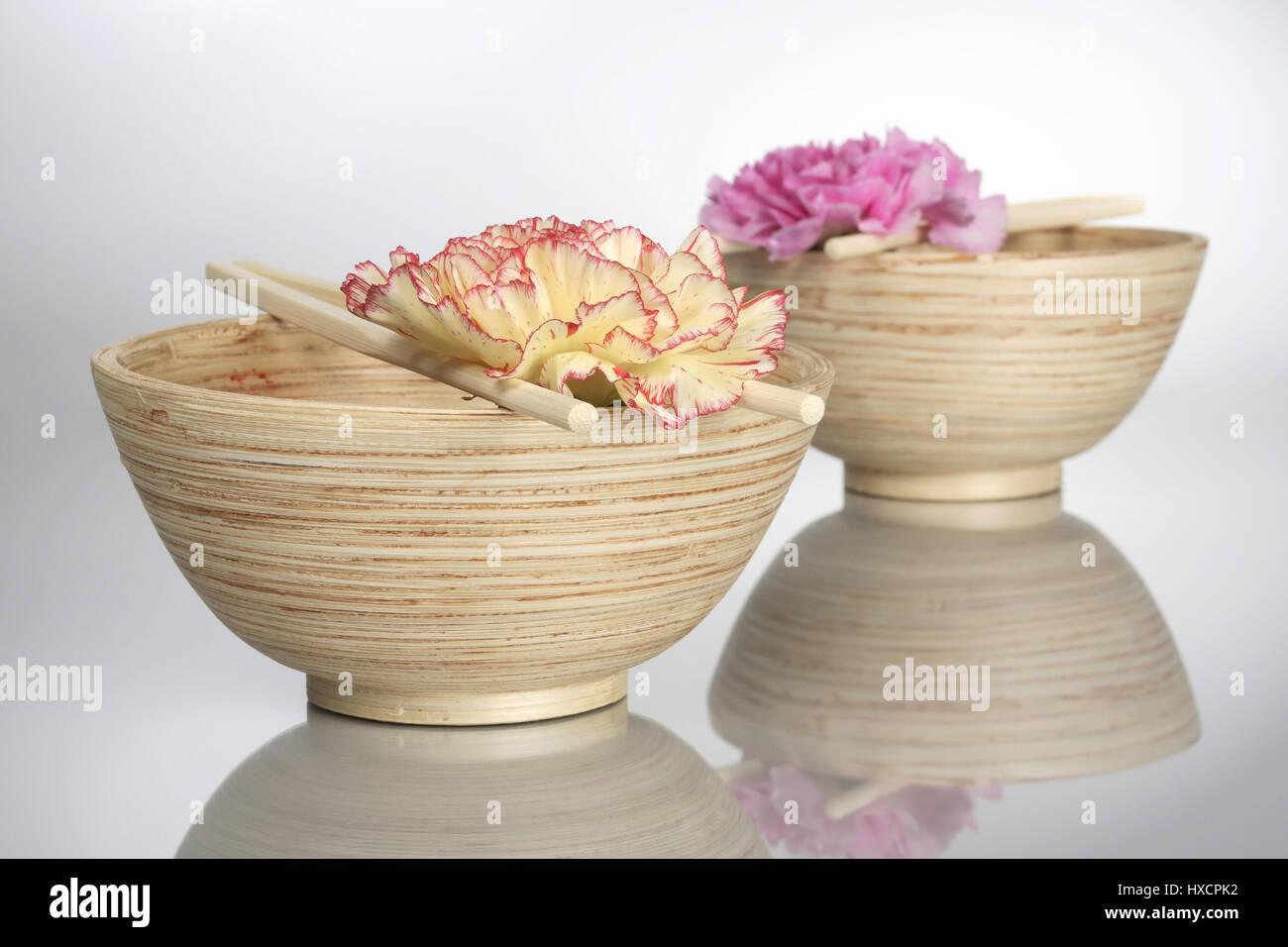Wooden bowls with rod and carnation blossoms, Holzschalen mit Staebchen und Nelkenblueten Stock Photo