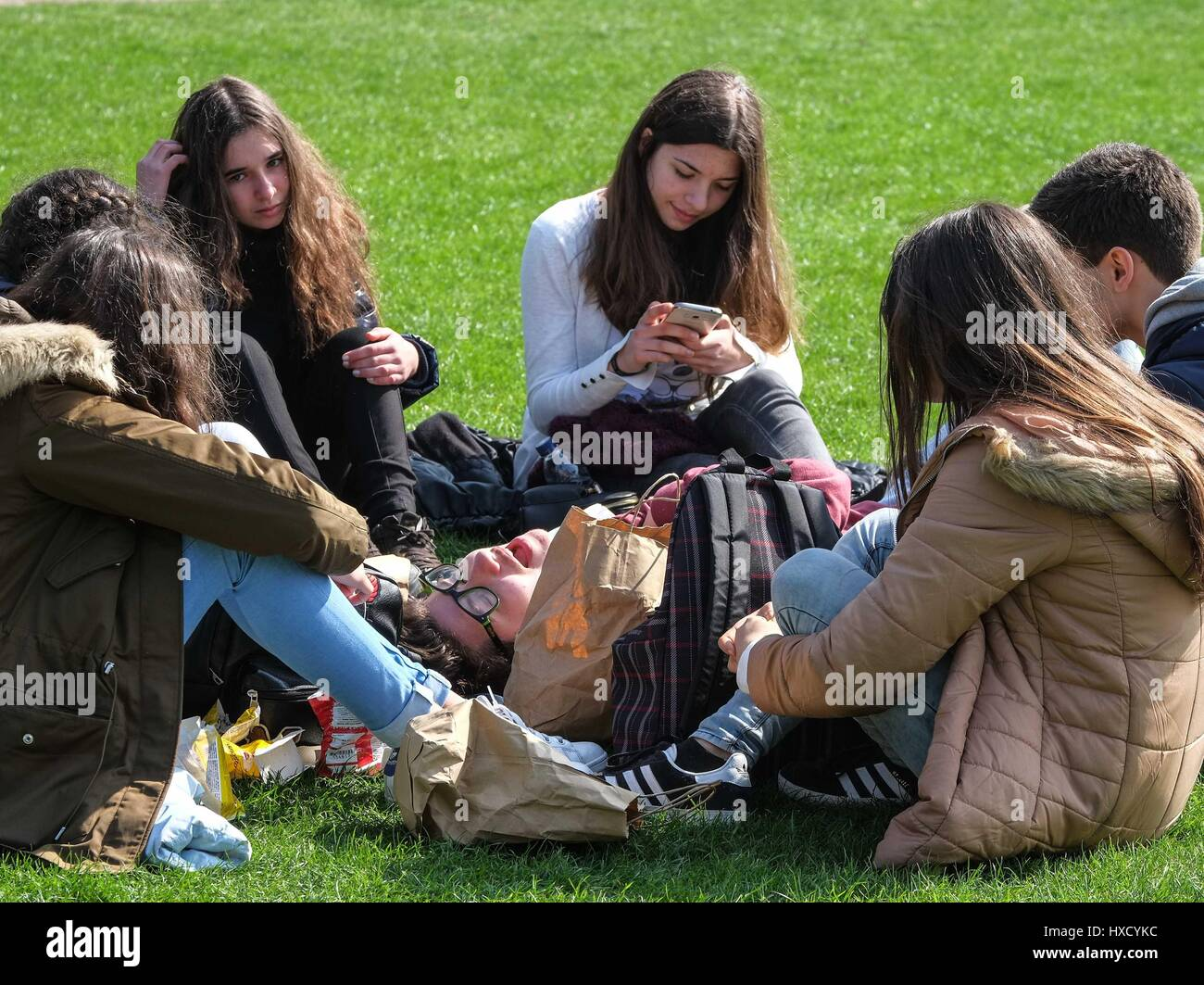 London, UK. 27th March 2017. Young women snoozes in the middle of a group of friends. Beautiful sunshine and tulips - Stock Image