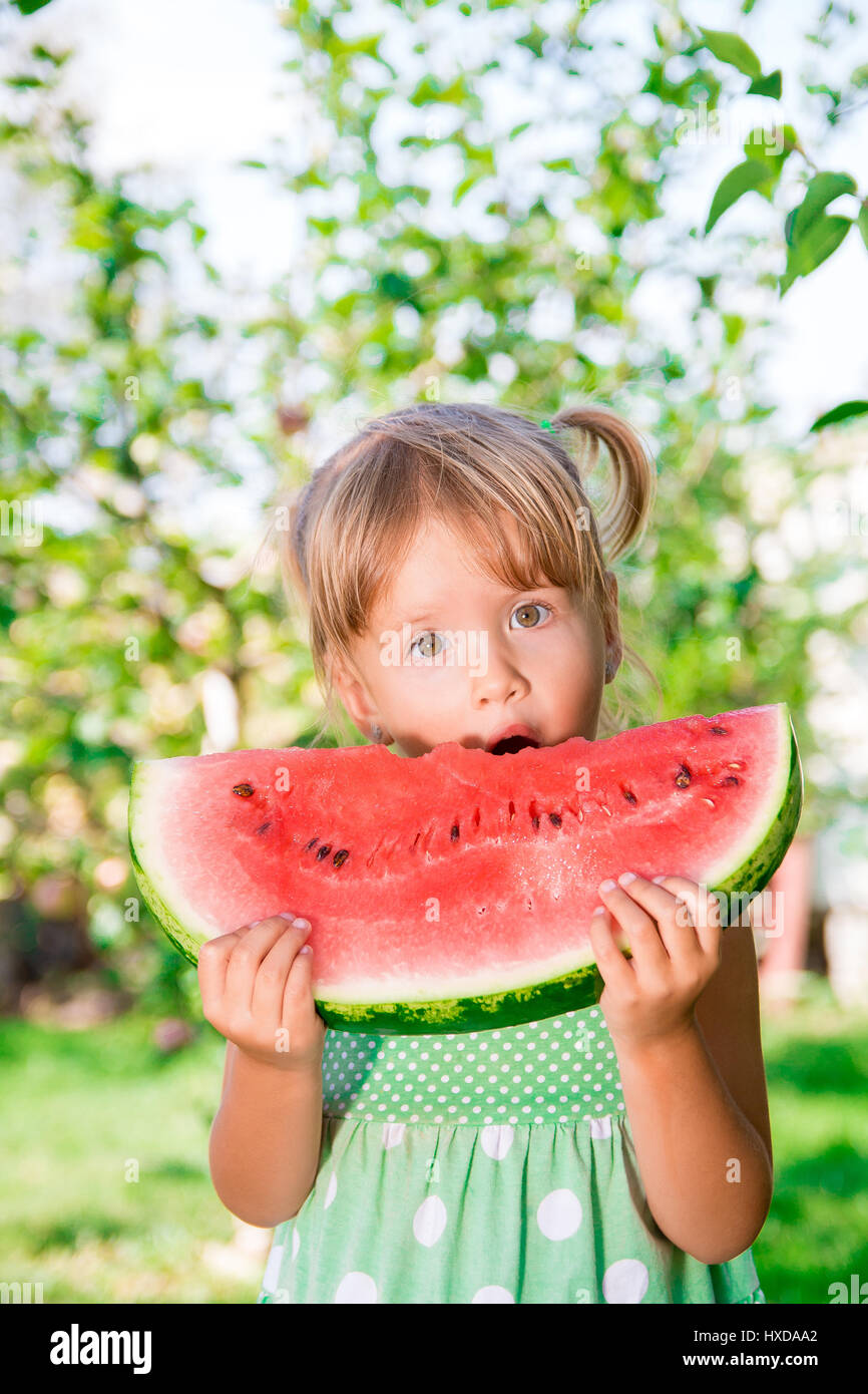 Little blonde girl with big slice watermelon in summer time in park, outdoor. Surprise child. Oops, wow - Stock Image