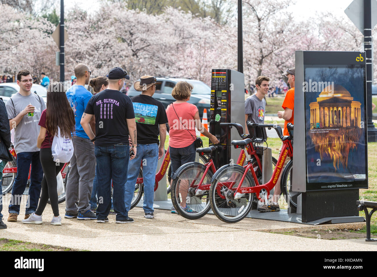 People rent bikes at a Capitol Bikeshare docking station in Washington, DC. - Stock Image