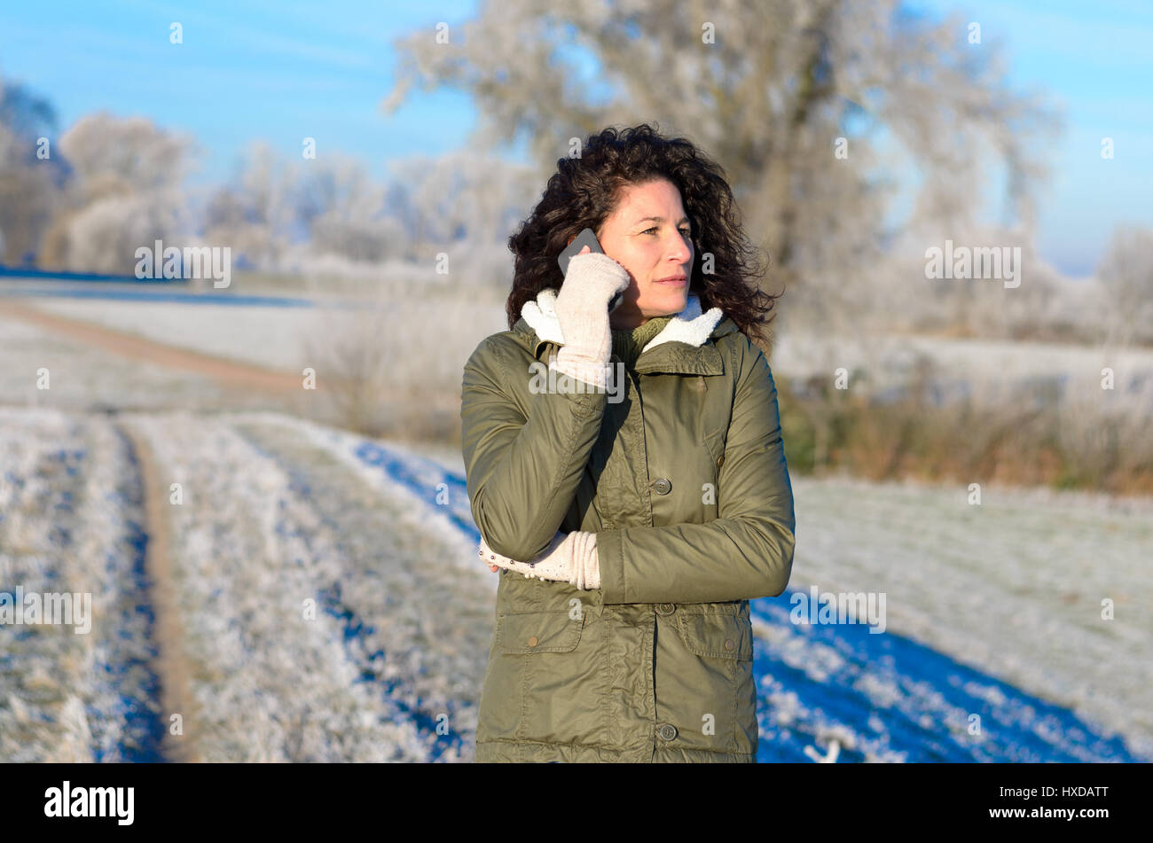 Young woman standing outdoors chatting on her mobile o a cold winter morning with a layer of hoar frost on the ground - Stock Image