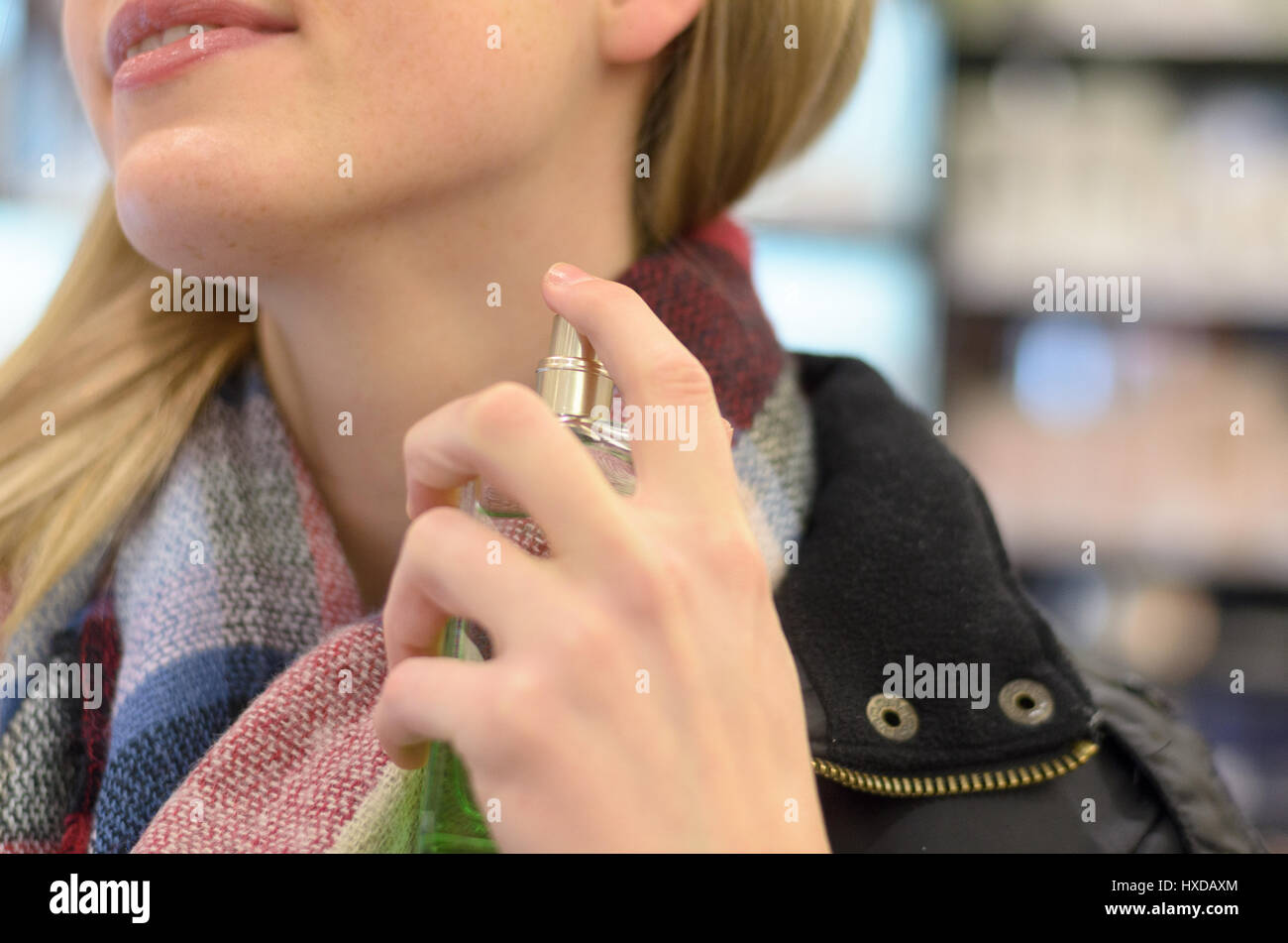 Young woman in a warm woolly knitted winter scarf spraying her neck with perfume in a store as she shops for Christmas Stock Photo