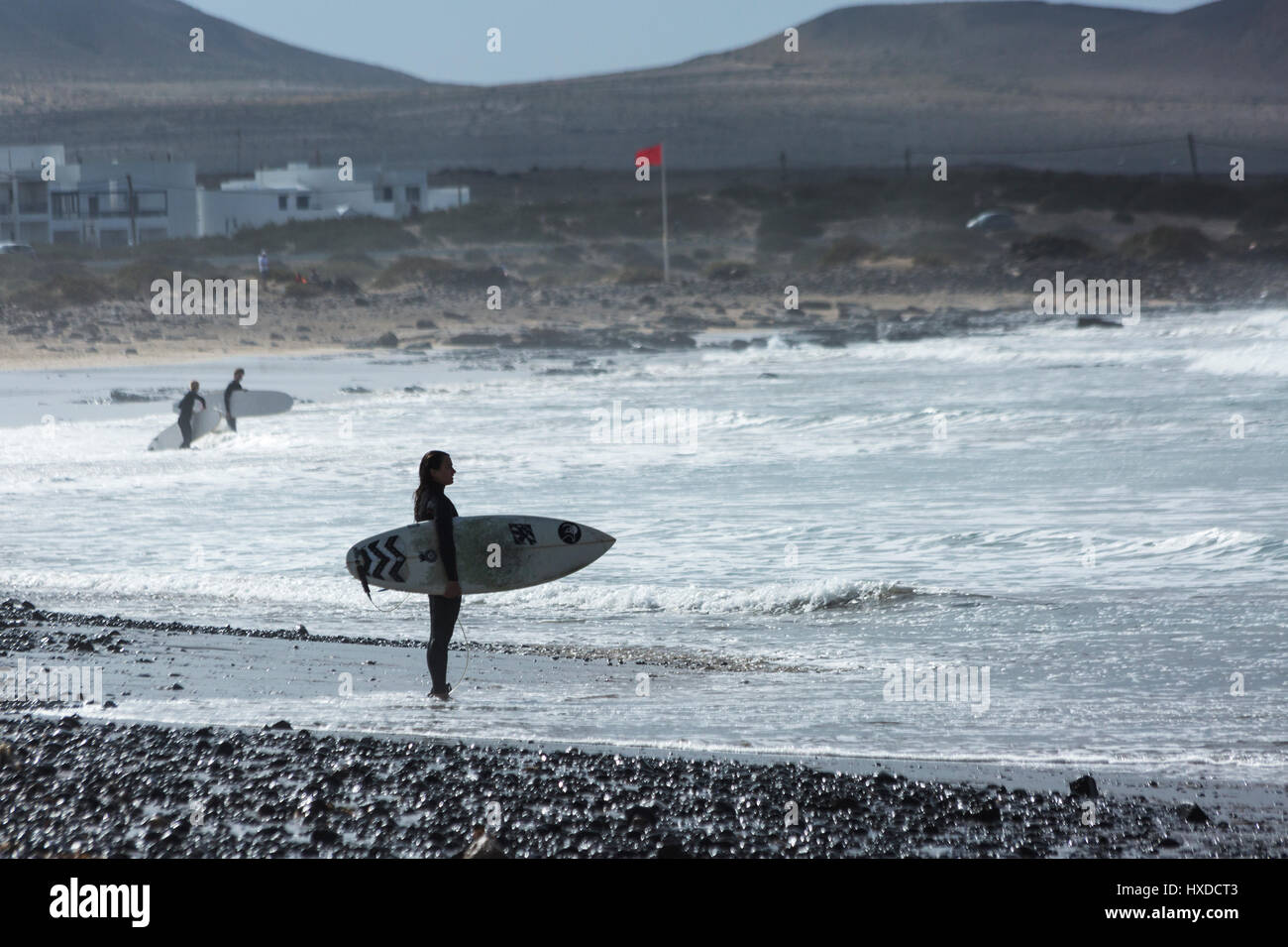 Girl surfer standing with surf board on Famara beach Lanzarote - Stock Image