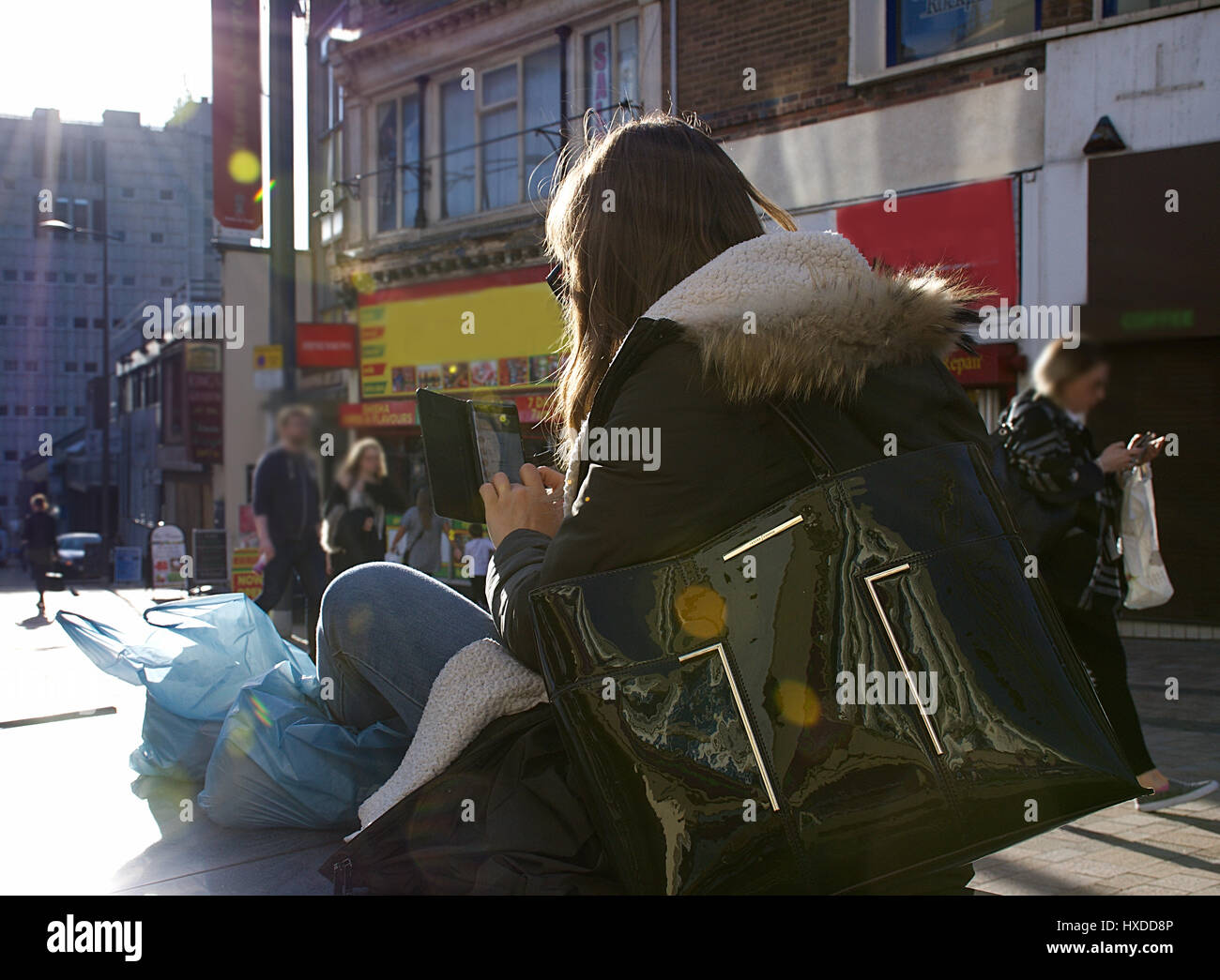 Young woman using her mobiles after shopping on high street in sunny spring day,Stoke on Trent,Staffordshire,United - Stock Image