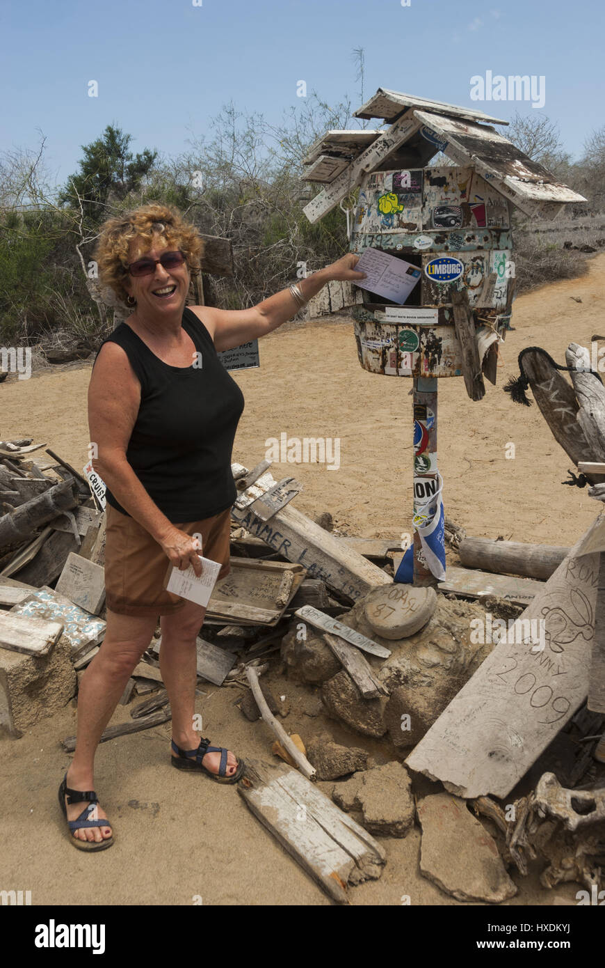 Ecuador, Galapagos, Floreana island, Post Office Bay, Visitor sending mail from whaler's postbox - Stock Image