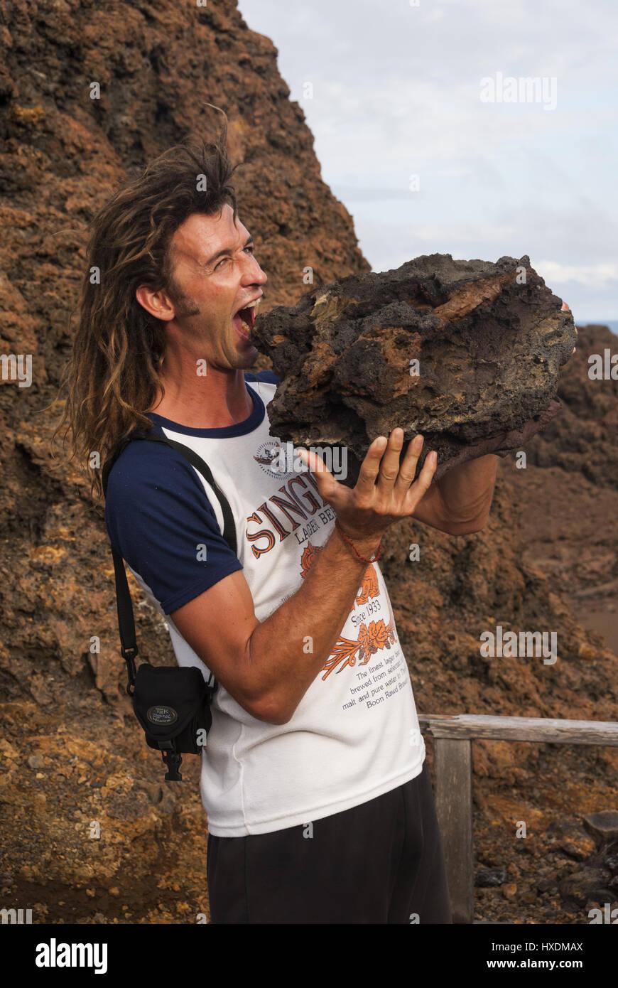 Ecuador, Galapagos, Bartolome island, Visitor with feather-light pumice boulder - Stock Image