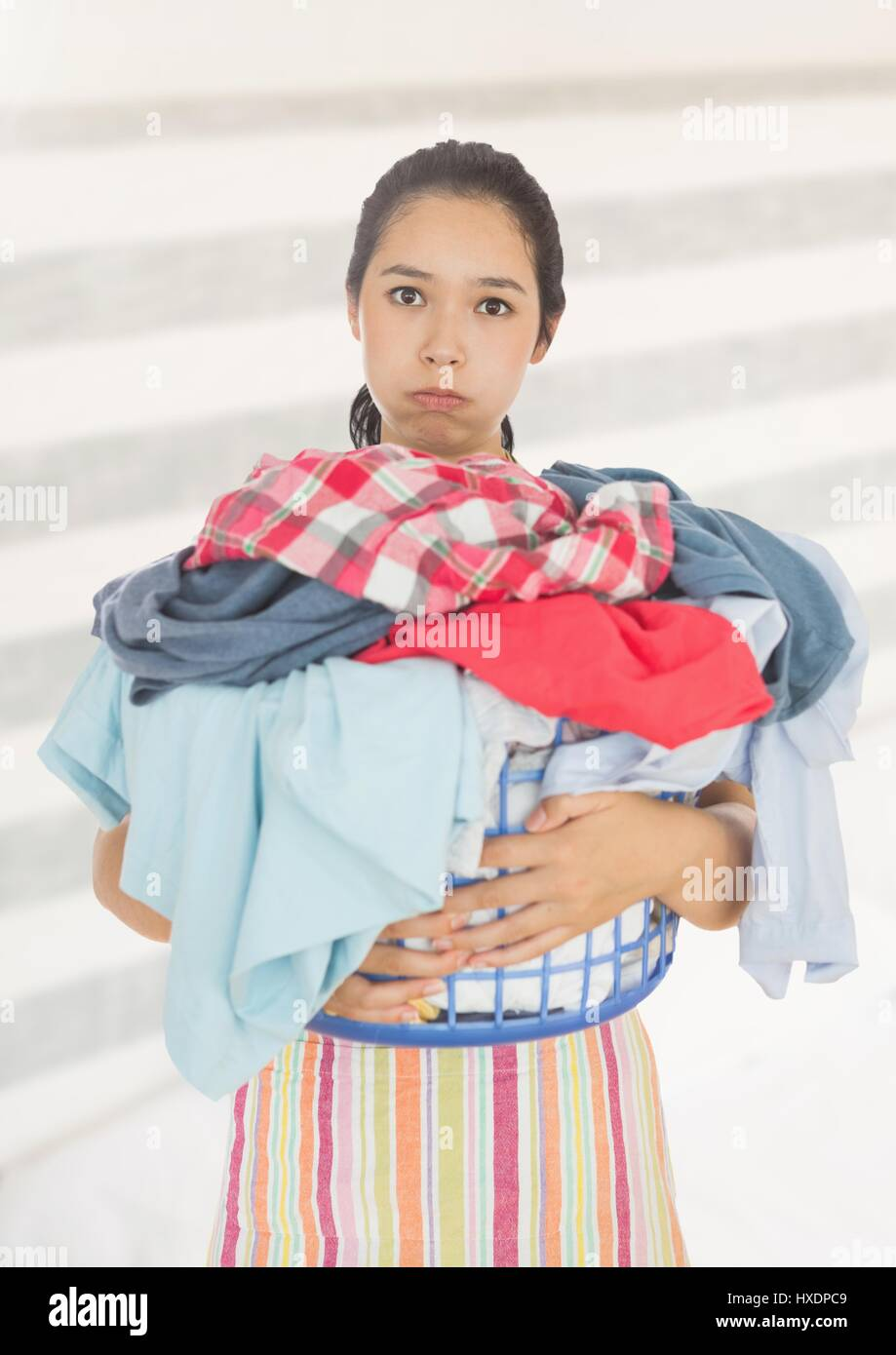 Digital composite of Tired upset woman with laundry basket against bright background - Stock Image