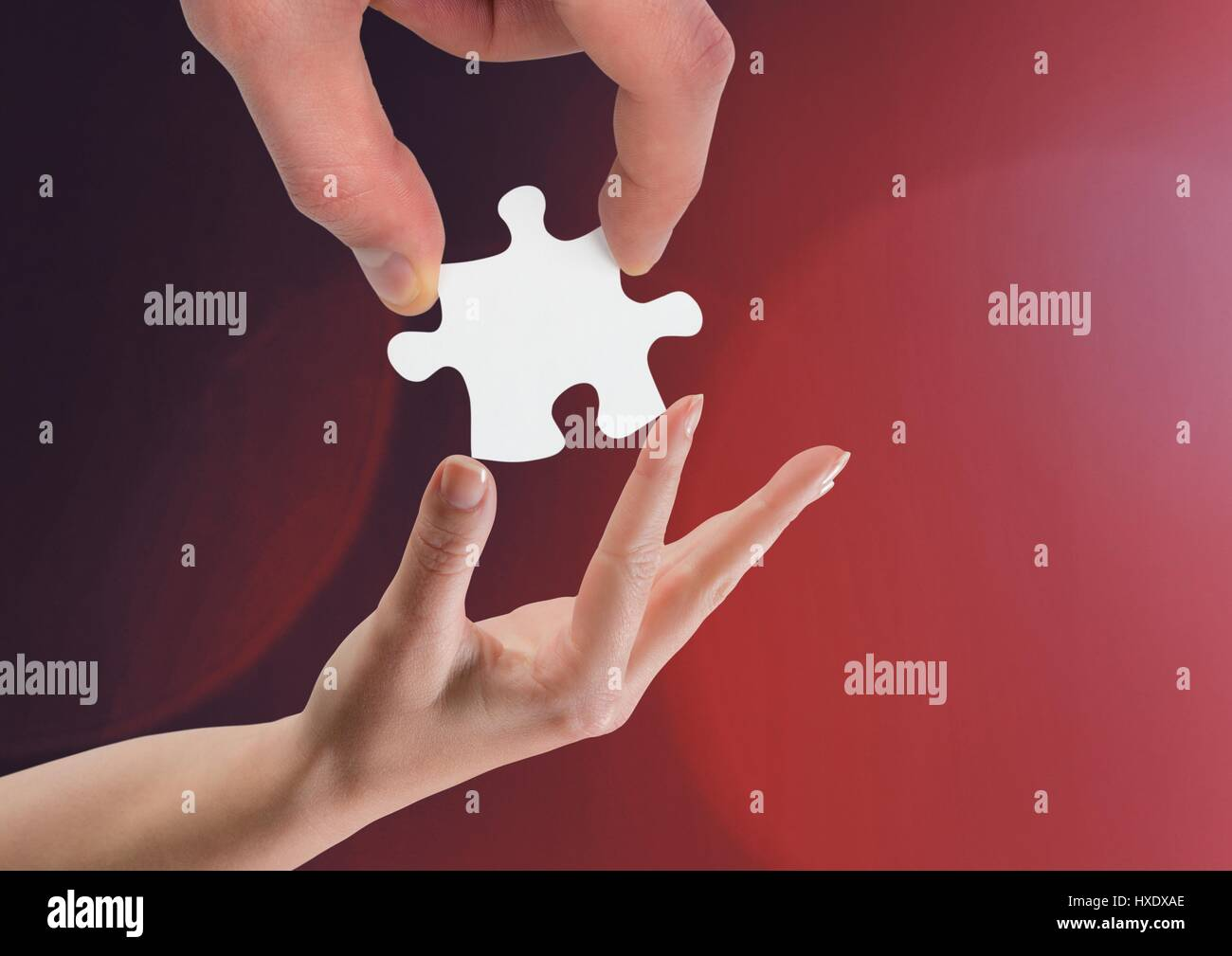 Digital composite of Hands holding jigsaw piece helping against red background Stock Photo