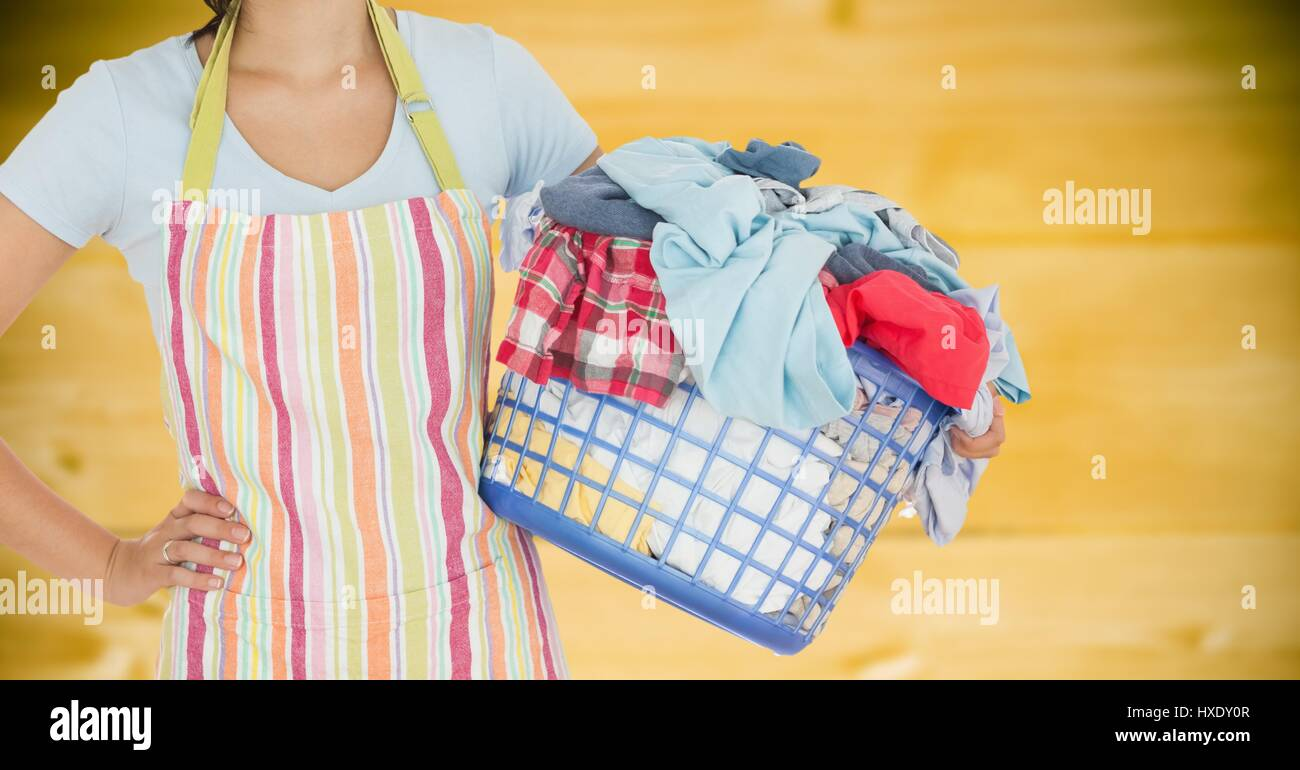 Digital composite of Woman in apron with laundry against blurry yellow wood panel - Stock Image