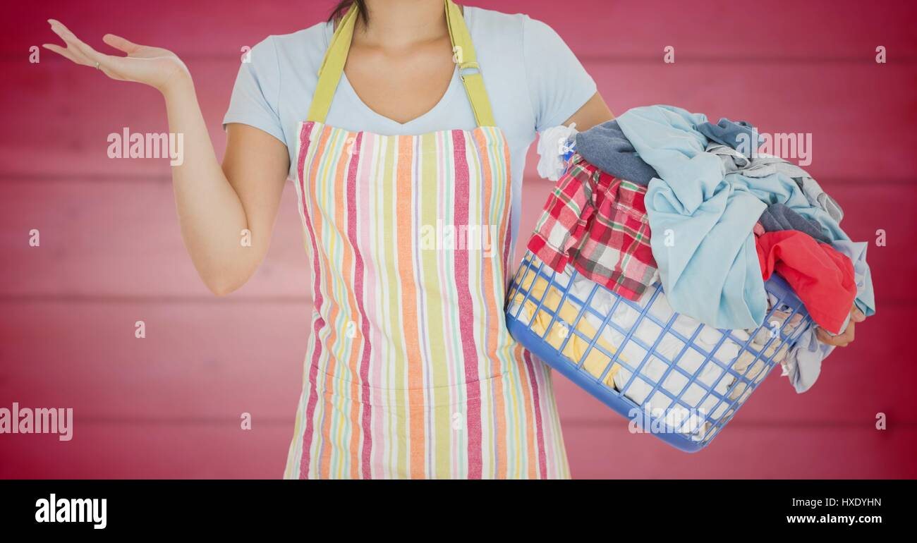 Digital composite of Woman in apron with laundry against blurry pink wood panel - Stock Image