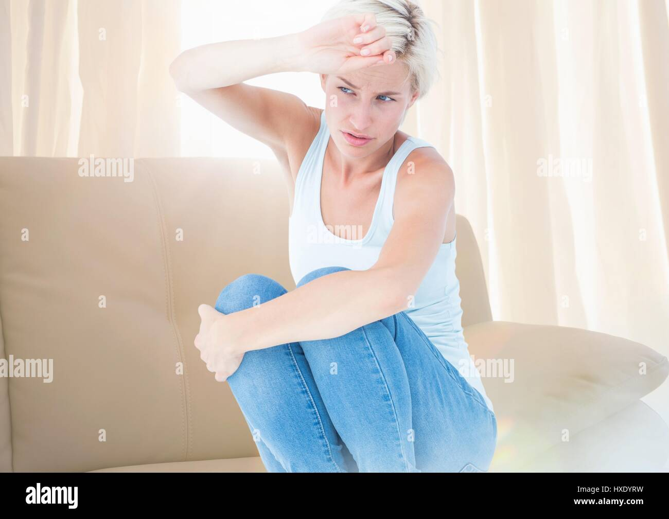 Digital composite of Sad  distressed afraid woman crouched near window light - Stock Image