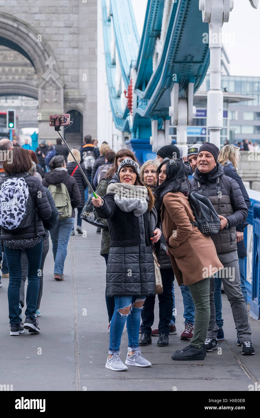 Tourists Friends Posing Photograph Selfie Stick Tower Bridge London - Stock Image
