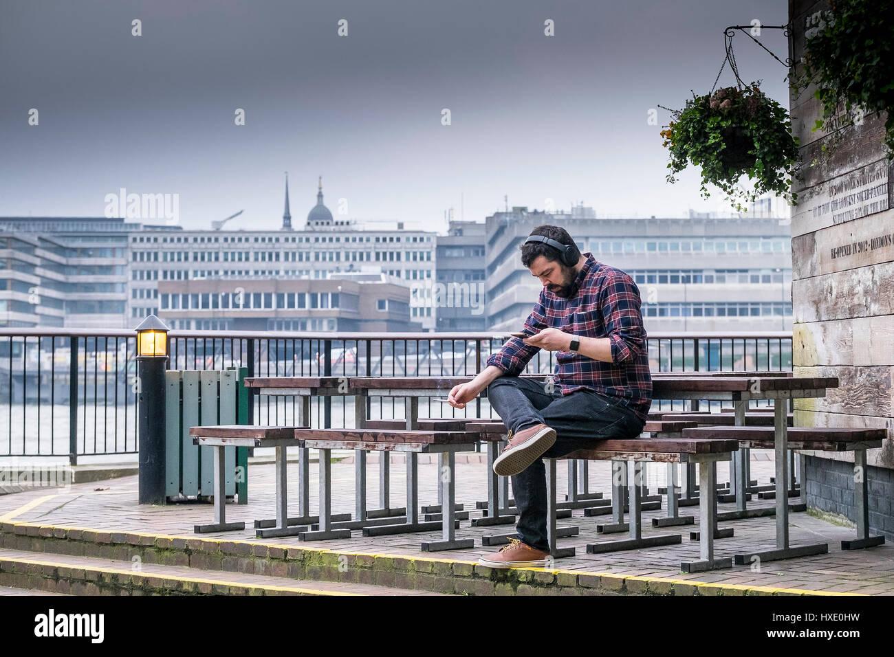 Man Leisure Sitting Smoking Earphones Relaxing Relaxation London - Stock Image
