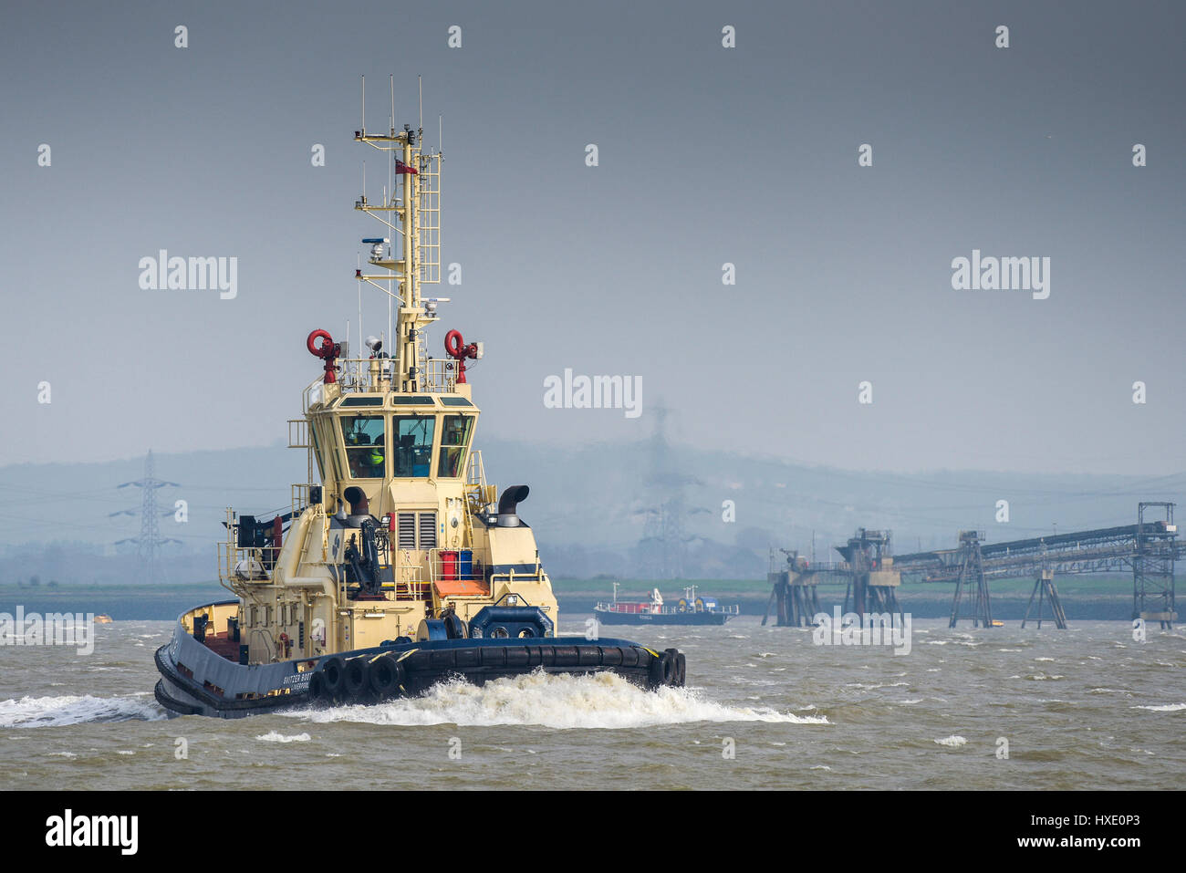 The tug Spitzer Bootle steaming sailing upriver on the River Thames in the UK. - Stock Image