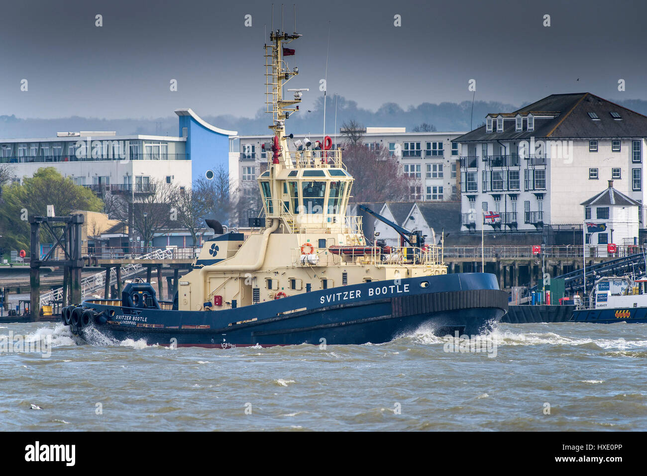 The tug Spitzer Bootle steaming upriver on the River Thames in the UK. - Stock Image
