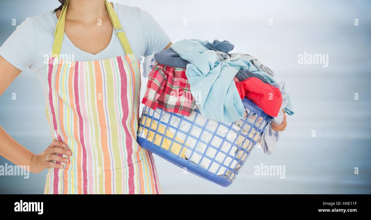Digital composite of Woman in apron with laundry against blurry grey wood panel - Stock Image