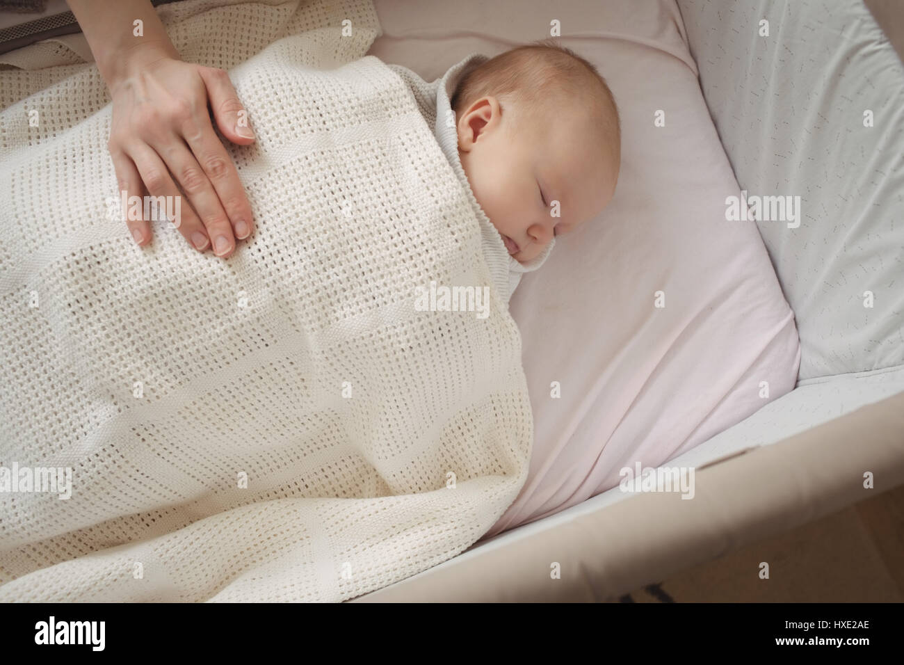 High angle view of mother hand on sleeping baby at home Stock Photo