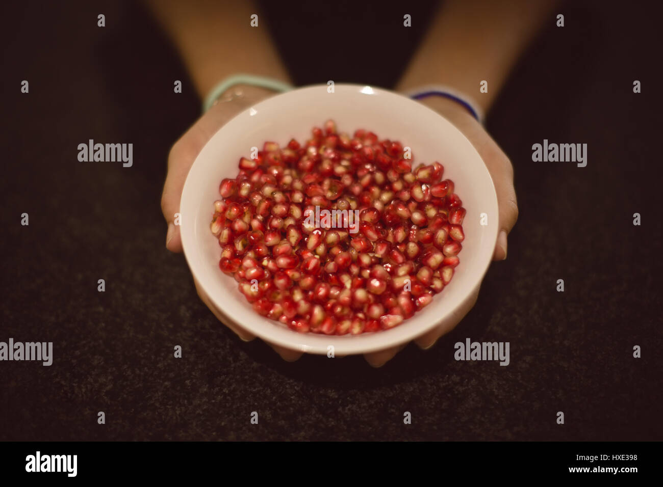 Close-up of hands holding bowl full of pomegranate - Stock Image