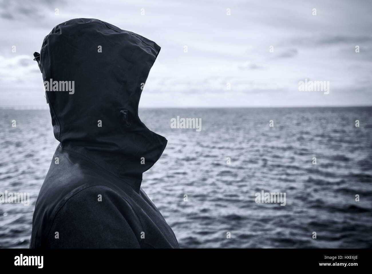 Faceless hooded person looking into distance at horizon over the sea water on cold windy winter day, anticipating - Stock Image