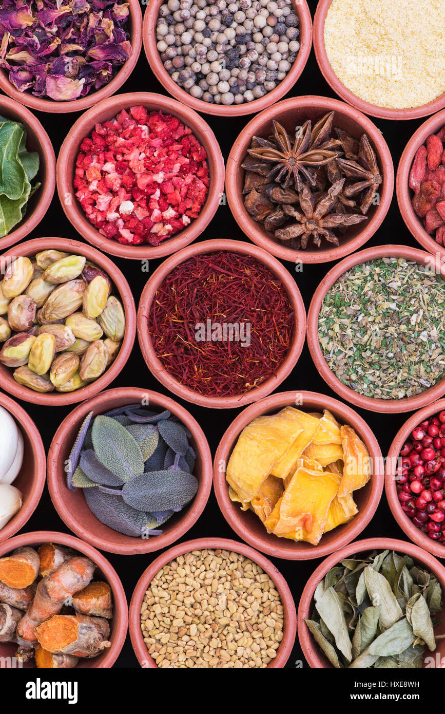 Cooking ingredients. Herbs, spices, nuts and seeds in round  terracotta pots pattern - Stock Image