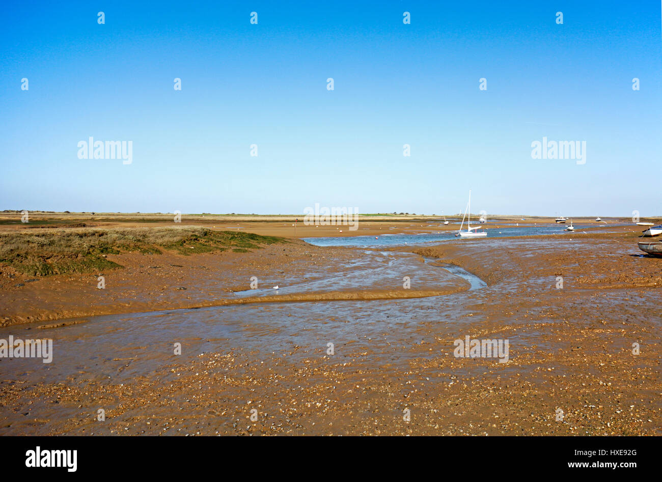 A view of an inlet at low tide in an Area of Outstanding Natural Beauty in North Norfolk at Brancaster Staithe, - Stock Image