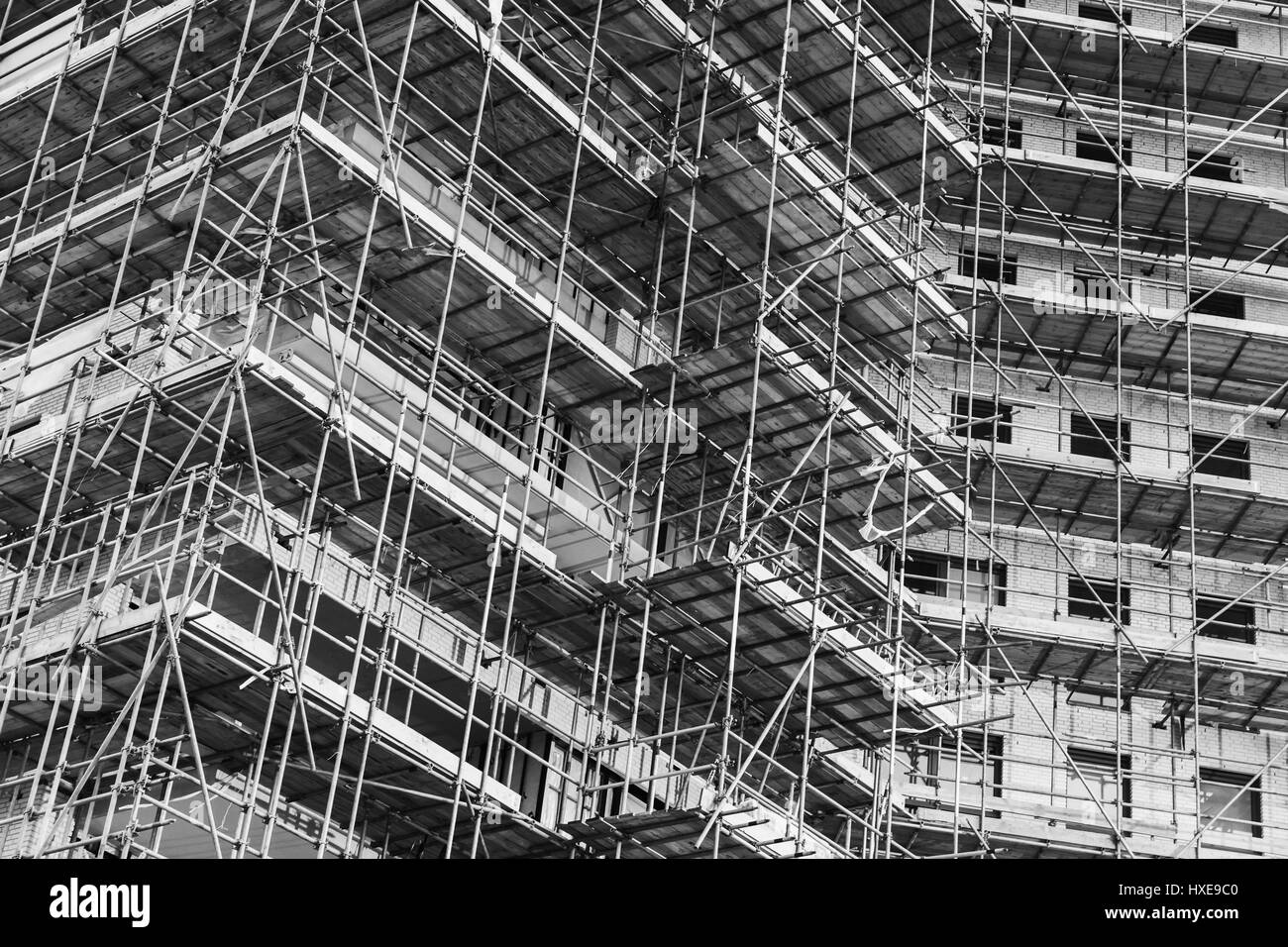 Modern living house is under construction, block of flats facade fragment with scaffolding structures, black and - Stock Image