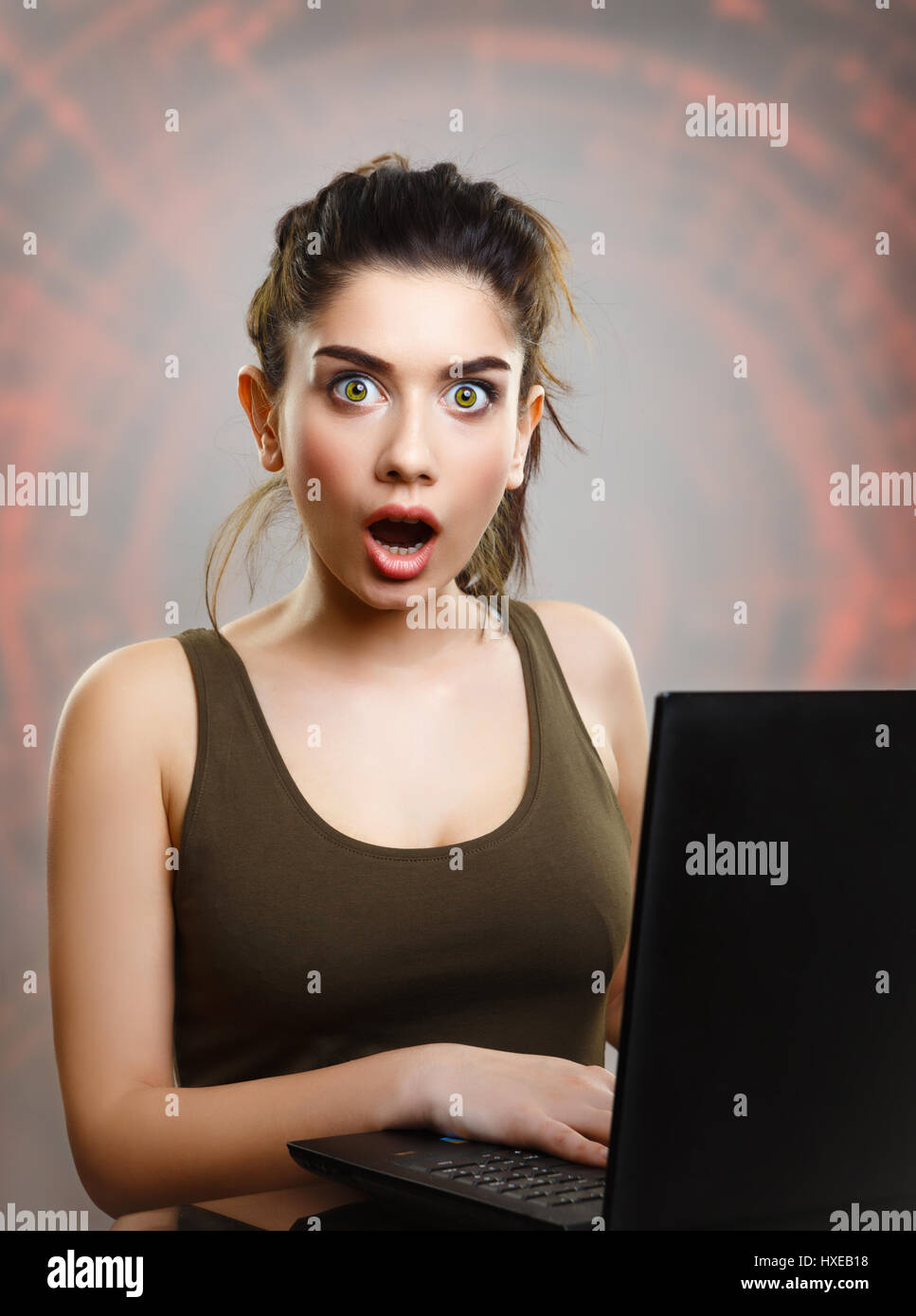 Young woman amazed and shocked by internet news search - Stock Image