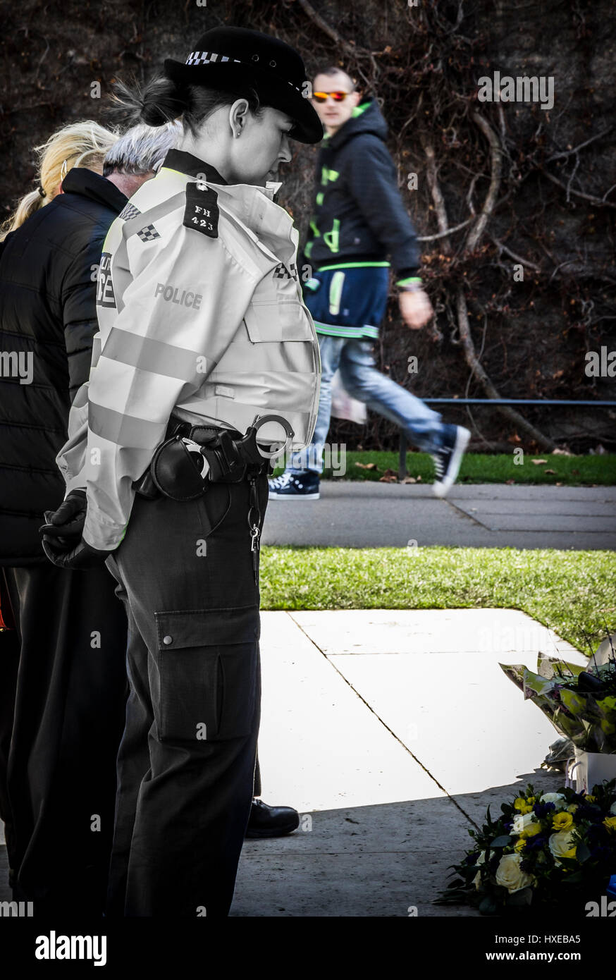 A lone female police officer in silent contemplation at the London Police Memorial, just days after the murder of - Stock Image