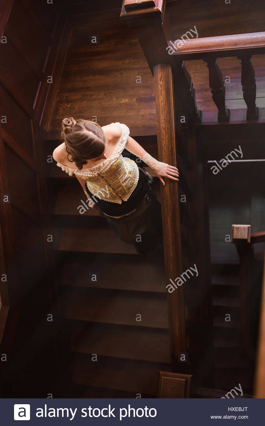 Young woman walking on staircase - Stock Image