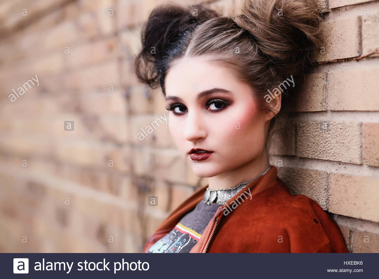 Portrait of a young woman leaning on a brick wall - Stock Image