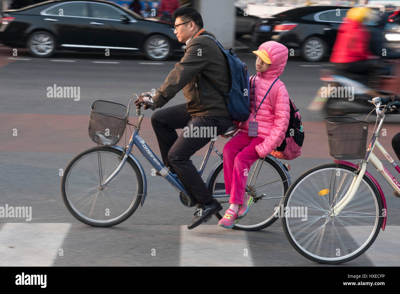 A Chinese father takes his girl on his bike to school in the morning in Beijing, China.  28-Mar-2017 - Stock Image