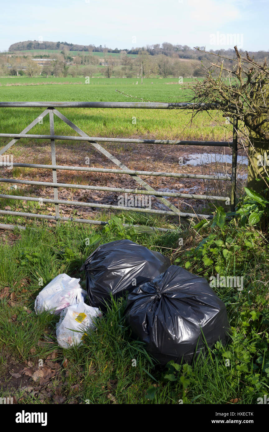 Rubbish bags left at a farm gate - Stock Image