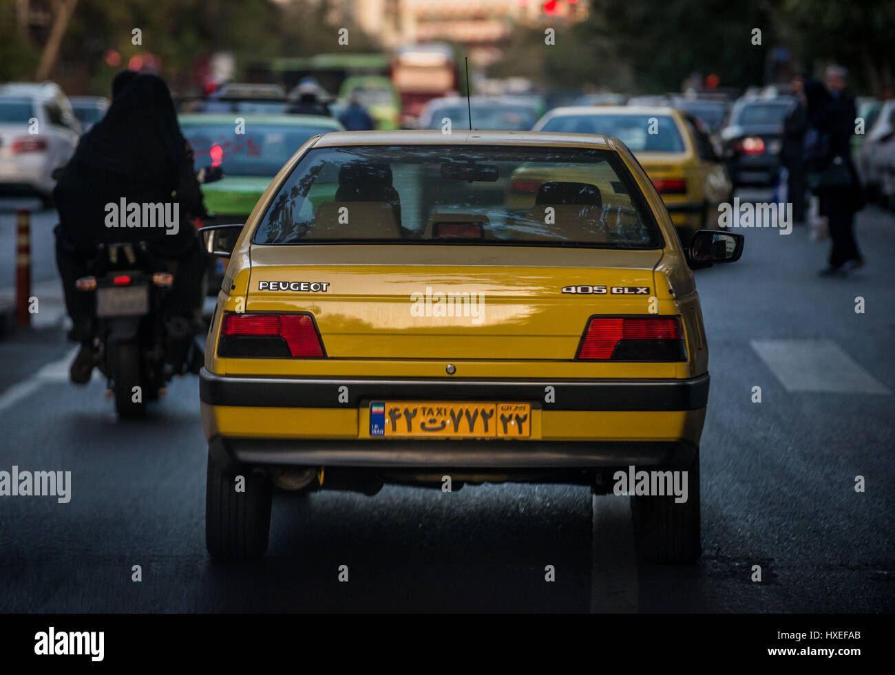 Yellow Peugeot cab on a street in Tehran city, capital of Iran and Tehran Province - Stock Image