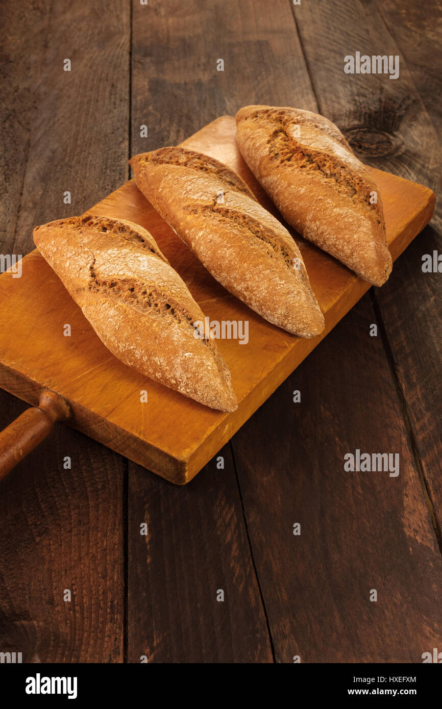 Loaves of rye bread on rustic board Stock Photo
