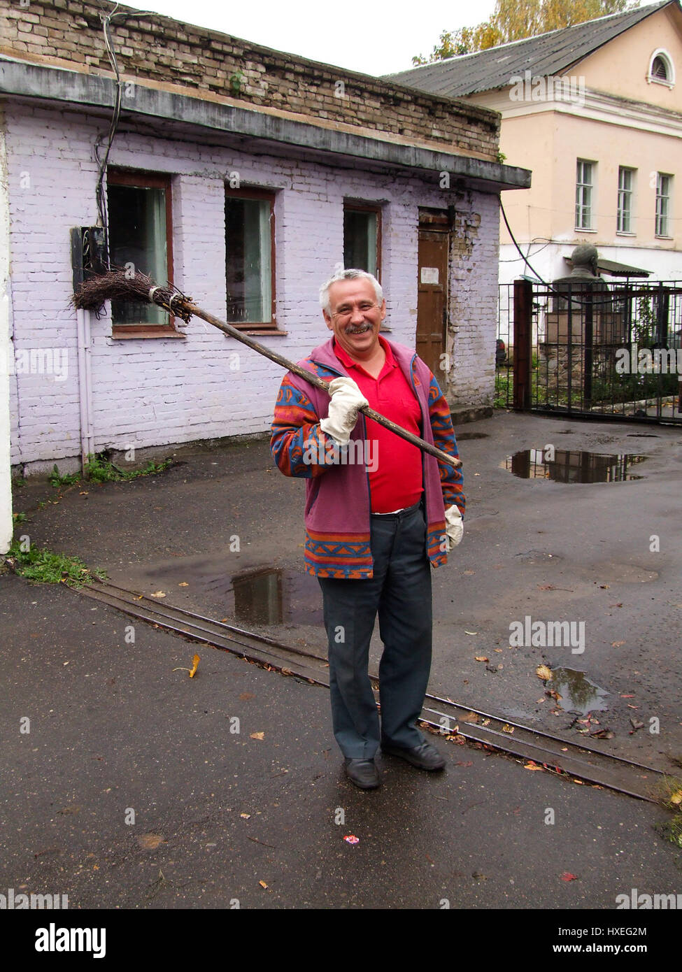 This workman with a stick broom was sweeping the parking lot of the KGB Headquarters complex in Vitebsk, Belarus. - Stock Image