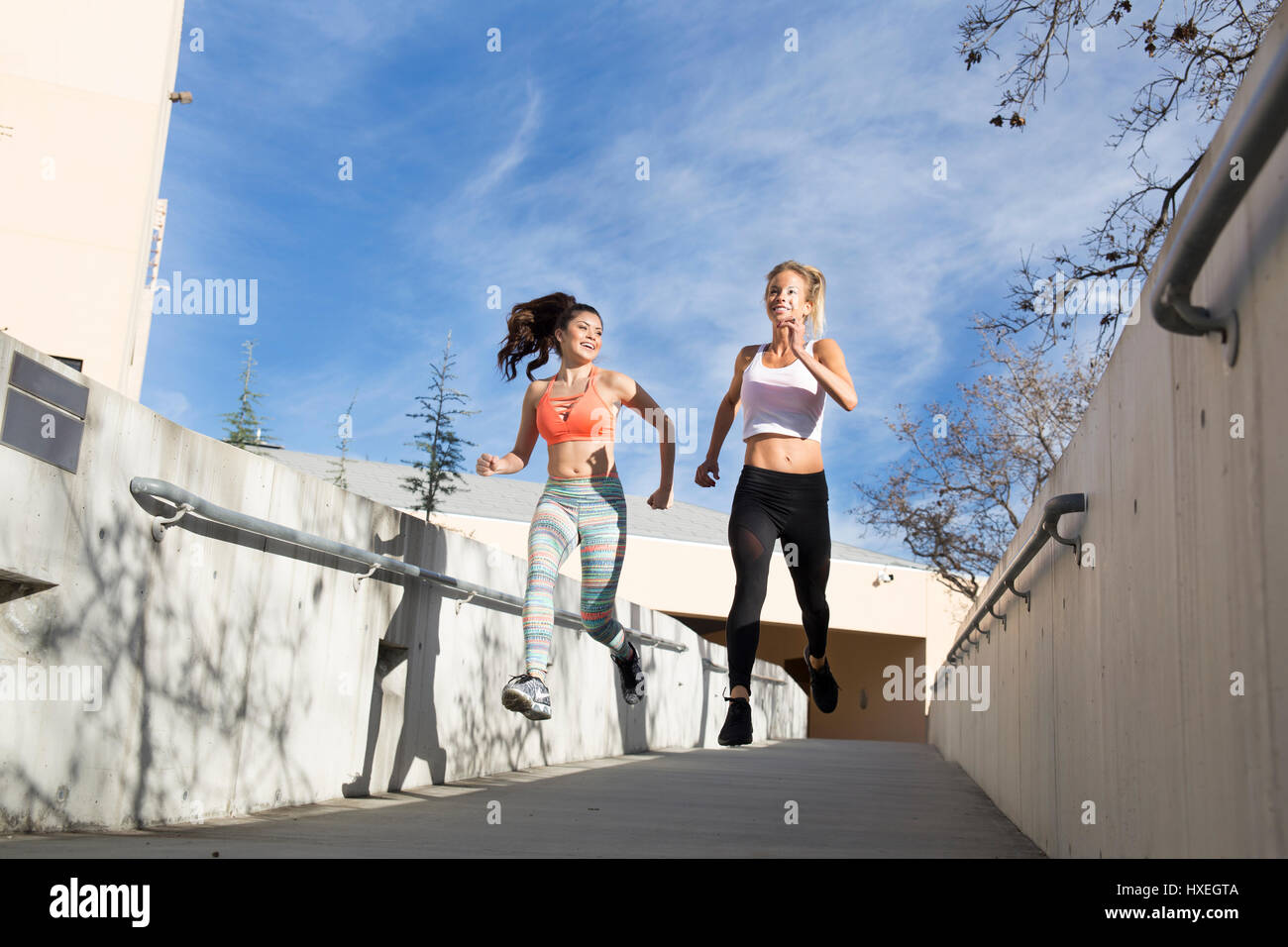 Girls workout and stretch together in a beautiful outdoor and urban setting. - Stock Image