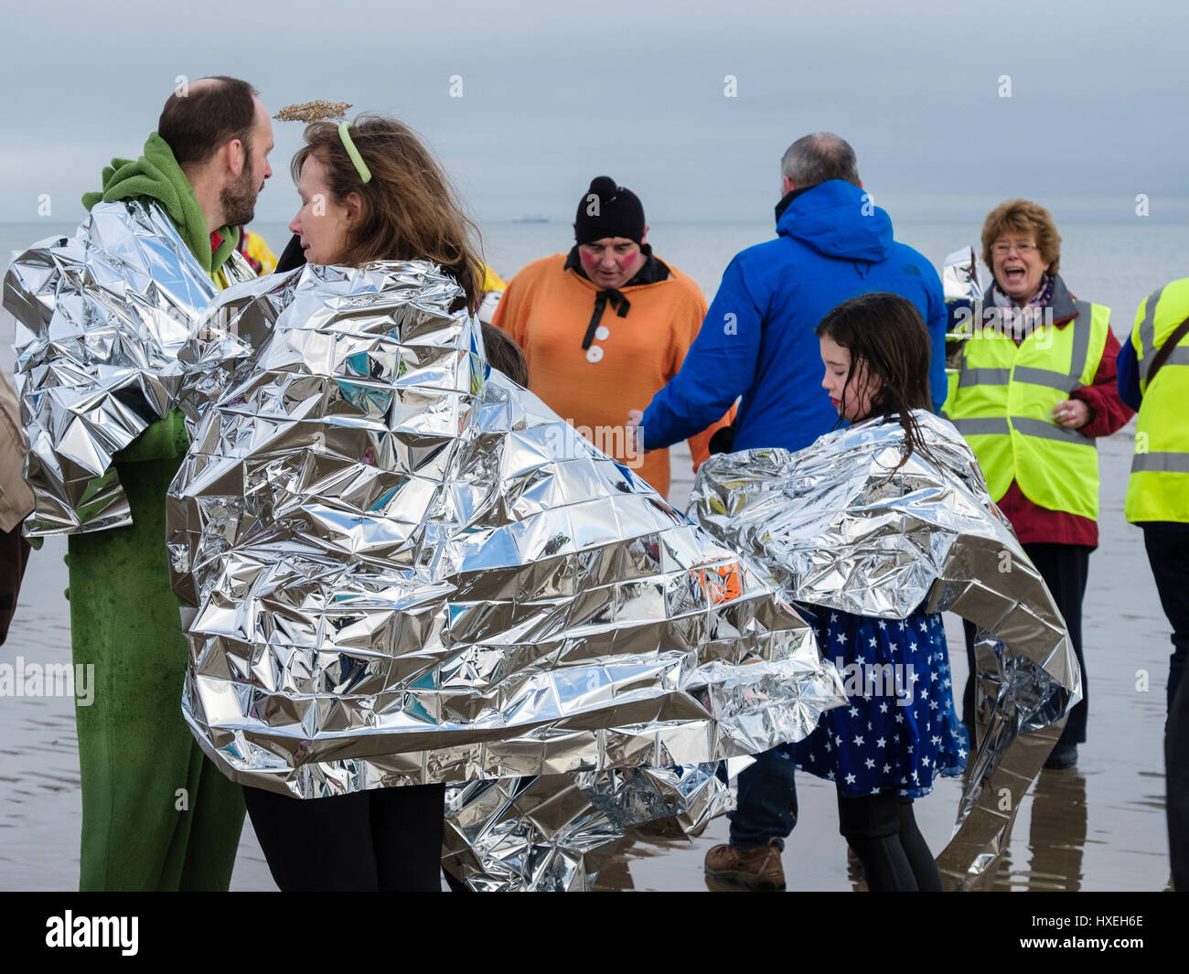 Wet swimmers wrapped in thermal foil emergency blankets to get warm after a sponsored swim in the sea for charity - Stock Image