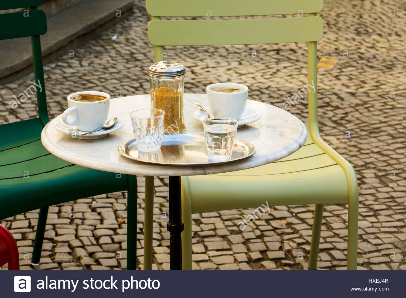 Cafe coffee shop table in berlin coffeehouse with two empty coffee cups, sugar and two glass water - Stock Image