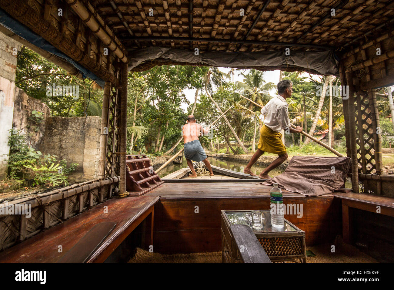 Two men punting environmentally friendly house boat in Kerala backwaters, southern India - Stock Image