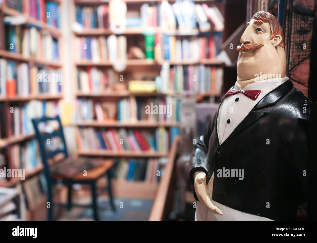 Butler puppet inviting to enter inside an old book store. - Stock Image