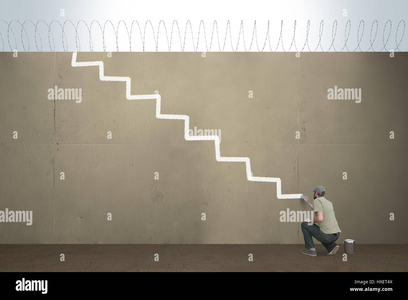 A man draws stairs on a border barrier - Stock Image