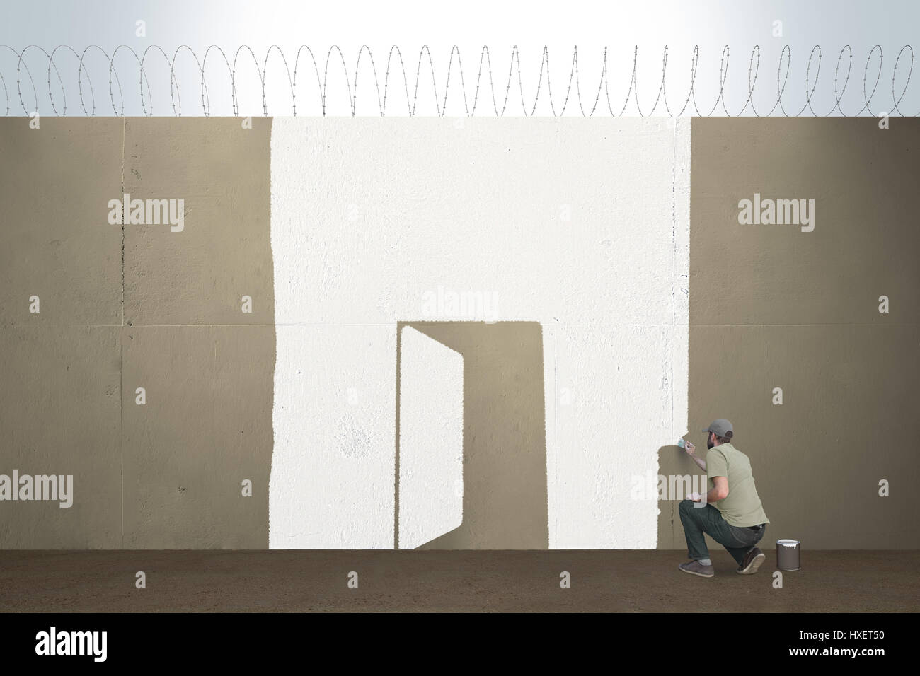 A man draws a open door on a border barrier - Stock Image