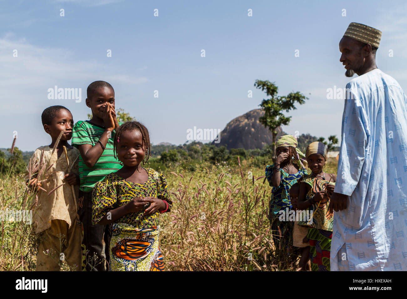 Elder of a small Fulani village close to Kaduna, Nigeria is welcomed by his children. - Stock Image
