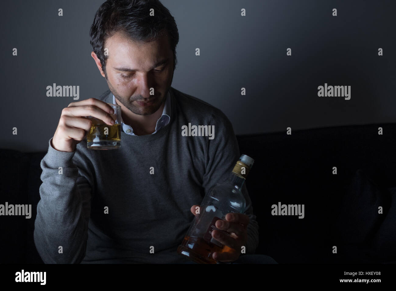 Depressed man abusing of alcohol trying to forget his problems - Stock Image