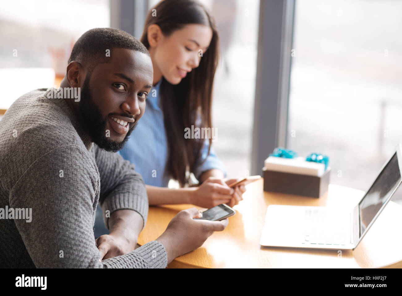 Young man and woman using smartphones at cafe - Stock Image