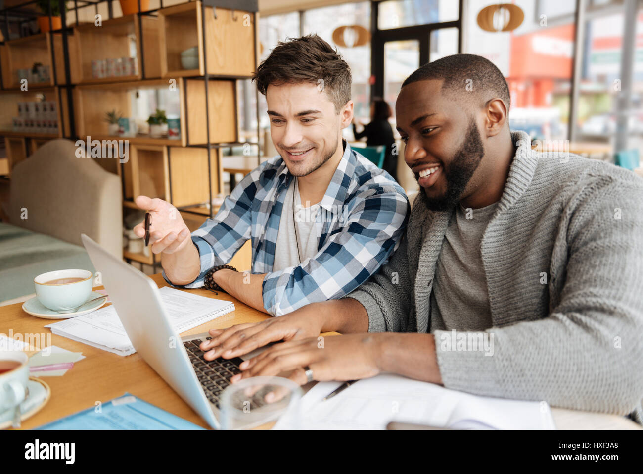 Cherfful students using laptop - Stock Image