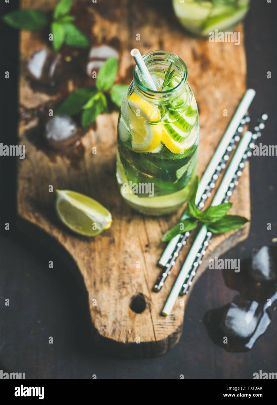 Citrus fruit and herbs infused sassi water on wooden board - Stock Image