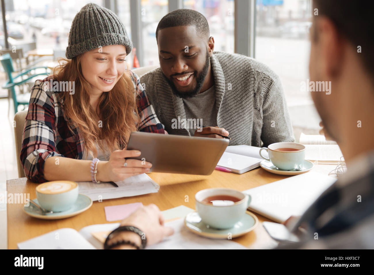Youngsters sitting with tablet in the cafe - Stock Image
