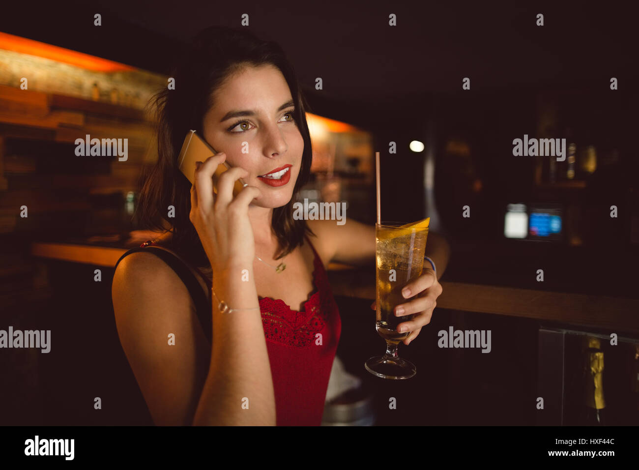 Beautiful woman talking on mobile phone while having cocktail at counter in bar - Stock Image